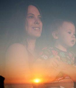 مادر و فرزند در کنار پنجره با شیشه کم گسیل و اشعه خورشید
