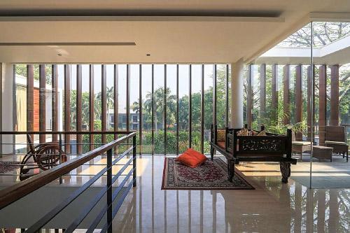 تصویر طبقه دوم ساختمان رویایی با دیوارهای شیشه ای و لورهای چوبی