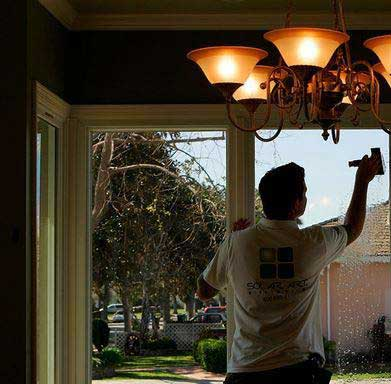 مردي درحال نصب برچسب عایق حرارتی شیشه ساختمان