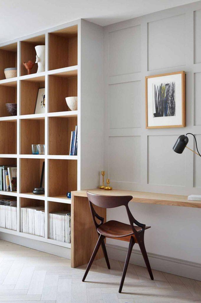 تصوير ميز و صندلی و قفسه کتابها در نشيمن با طراحی داخلي مدرن