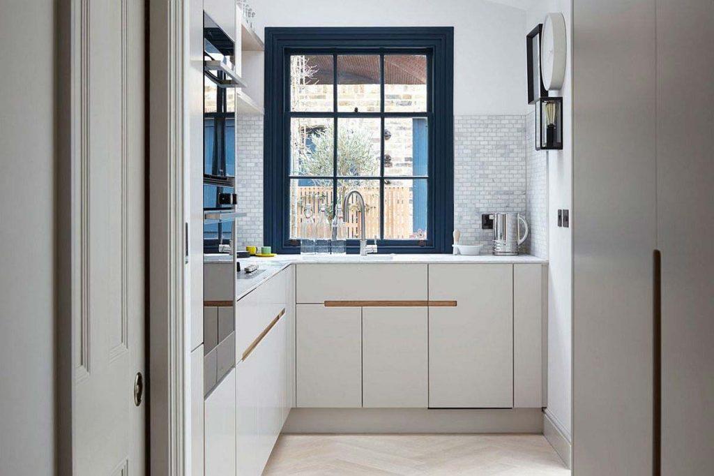 نمايی از آشپزخانه و کفپوش وی شکل و کابينت های آن در طراحی داخلی مدرن