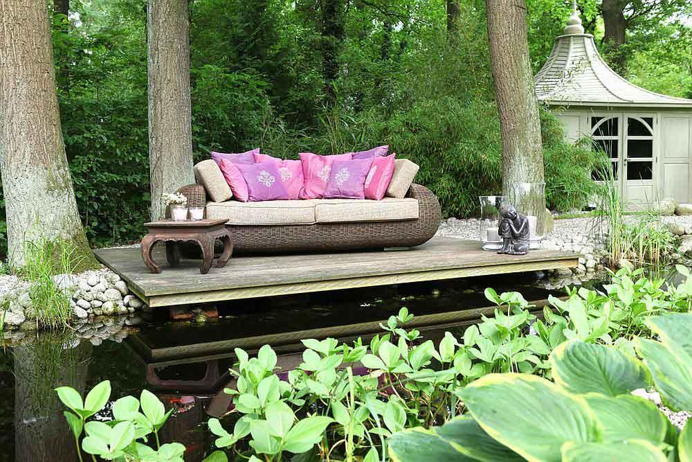 کاناپه بر روی سکوی چوبی به همراه مجسمه بودا بر روی برکه در باغ کلاسیک