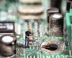 تصویر مدار پردازشگر سیستم کنترل هوشمند موتورخانه ساختمان و دونفر در حال ساختن مدار
