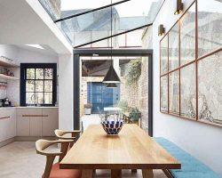 تصوير طراحی داخلی مدرن آشپزخانه و ناهارخوري که به حياط خلوت متصل شده است