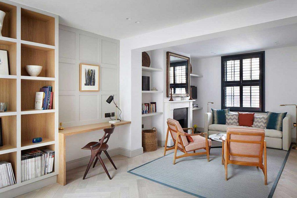 نمای باز فضای نشيمن با مبلمان کلاسيک و شومينه و ميز و صندلی مطالعه و بخشی از قفسه های کتاب