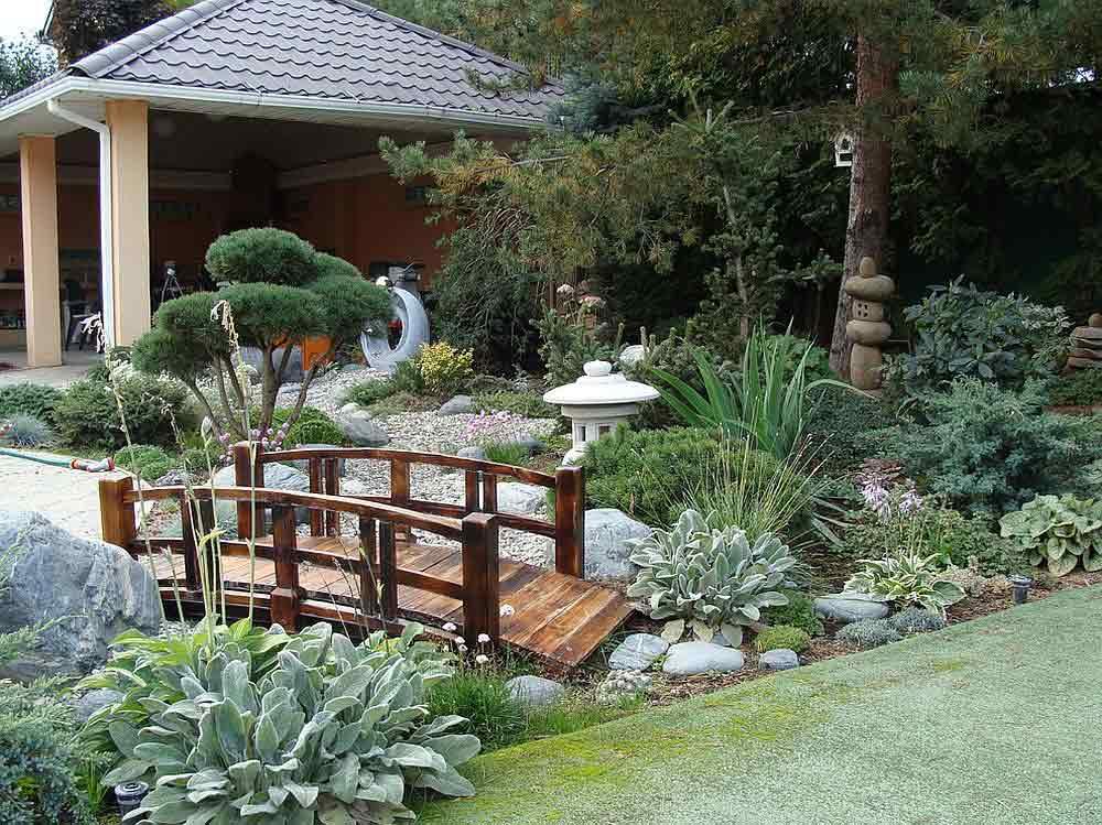 پل چوبی بر روی جوی آب در باغ رویایی به سبک ژاپنی