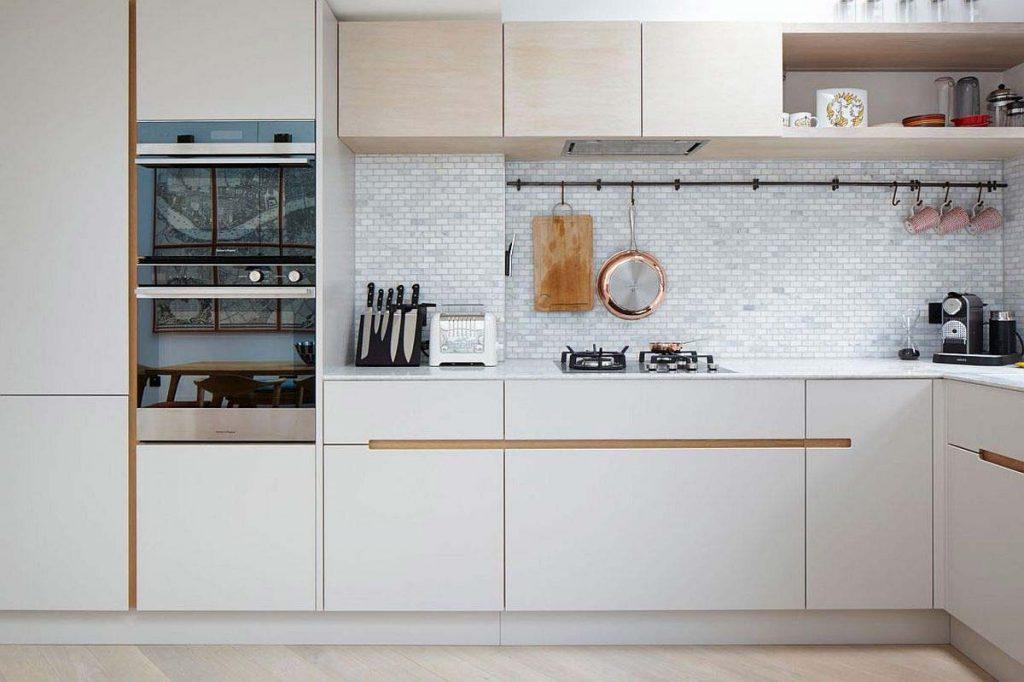 نمايی از داخل اشپزخانه با کابينت های سفيد و شيک و کاشيکاری سفيد رنگ