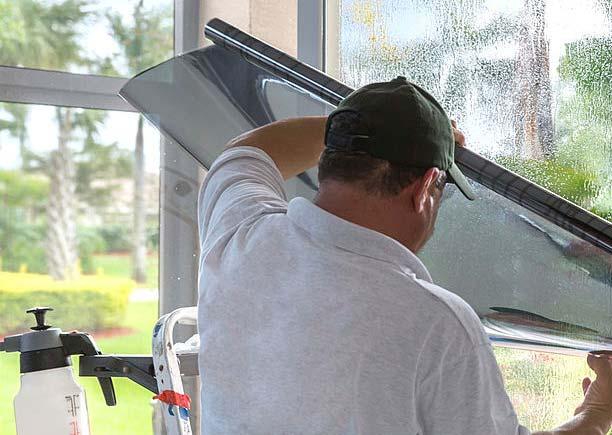 مردي در حال نصب برچسب پنجره
