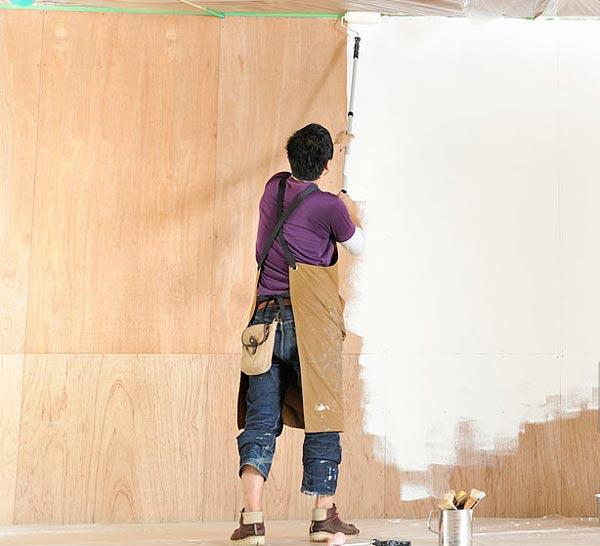 فردي در حال رنگ کاري چوب با رنگ ساختمان