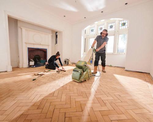 یک آقا در حال کفپوش کردن کف یک منزل می باشد