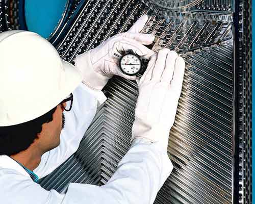 مهندس مشغول اندازه گیری فاصله و عمق شیار صفحات انتقال دهنده گرمایی تخت