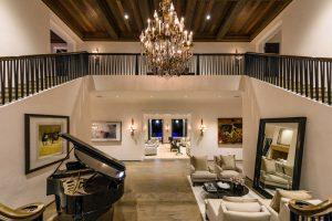 پيانو و آيينه بزرگ کنار مبل های راحتی در سالن خانه لوکس