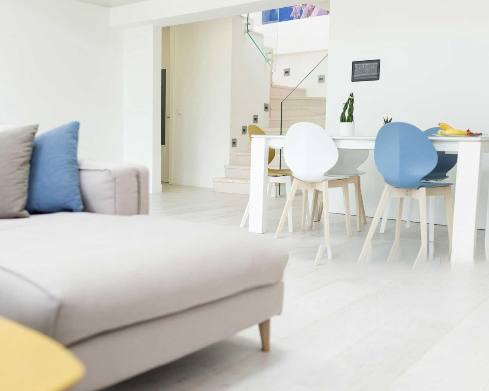 ترموستات اتاقی هوشمند و یک صندلی آبی و سفید و تخت خواب کرمی و تعدادی موز روی میز
