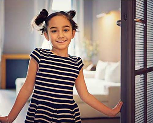دختر بچه ای که پنجره خانه را باز نگه داشته است