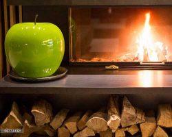 سیب سبز سلامتی در کنار شومینه هیزمی