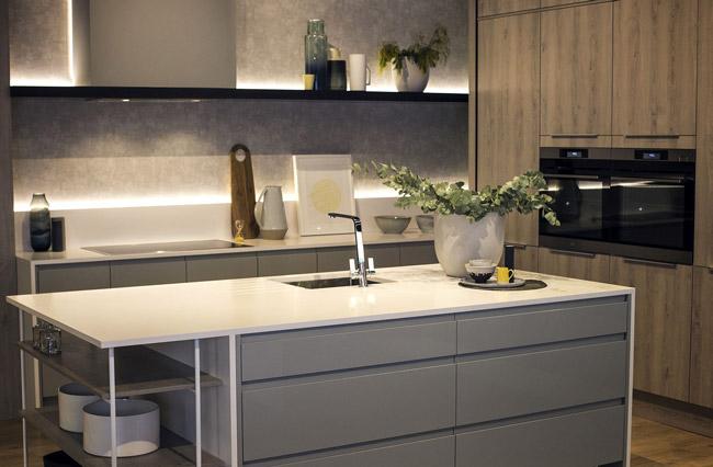 آشپزخانه با رنگ های تیره که با چراغ های LED نواری روشن شده است