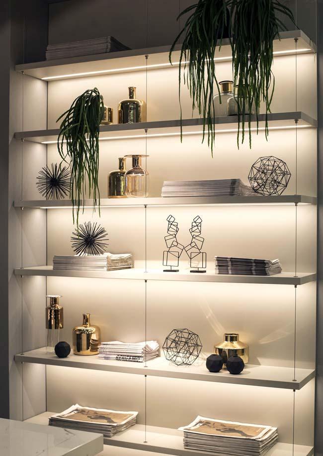 قفسه های اپن که برای نمایش قطعات دکوری استفاده شده و با چراغ های ال ای دی نواری روشن شده اند