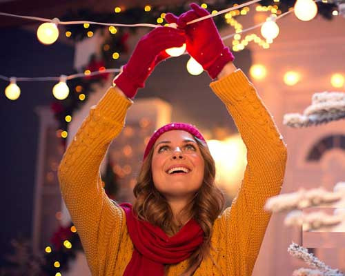 خانمی در حال بستن لامپ به ریسه های کریسمس