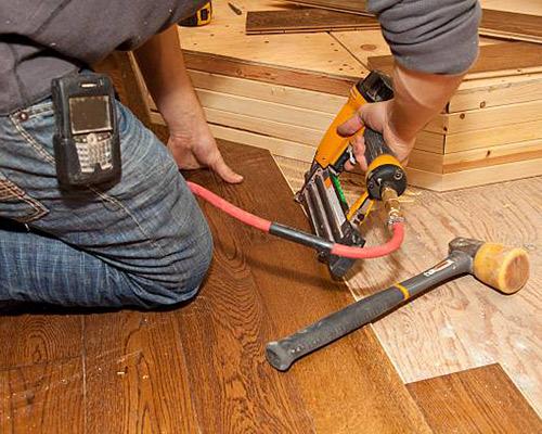 یک آقا در حال نصب کفپوش چوبی می باشد