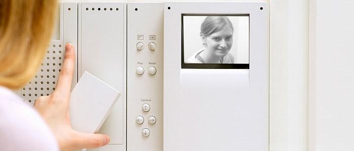 شخصی در داخل منزل توسط آیفون تصویری يا درب بازکن تصویری فردی که زنگ در را زده می بیند
