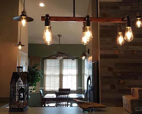 لامپ فیلامنتی خمره ای و میز ناهارخوری چوبی قهوه ای و قفس پرنده چوبی