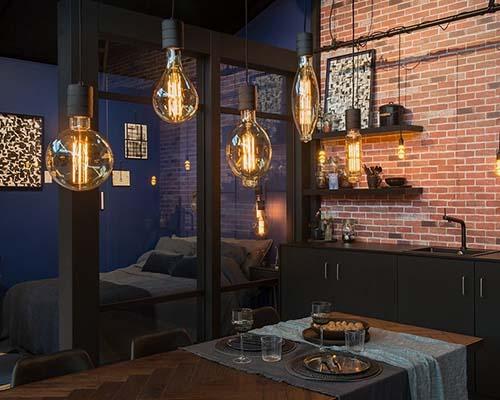 انواع لامپ های فیلامنتی در اتاق خواب و تخت خواب مشکی و میز چوبی قهوه ای