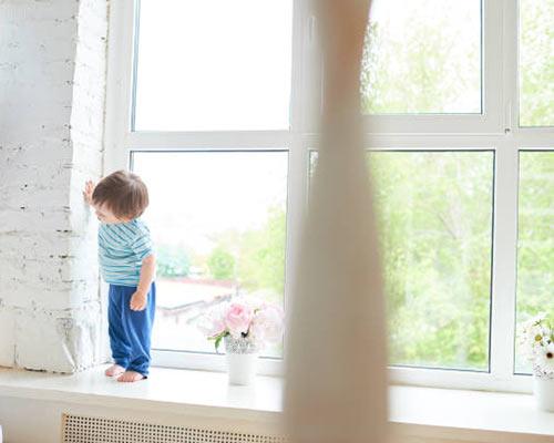 کودکی در مقابل پنجره نور گذر بسیار زیبا و منحصر به فردی ایستاده است