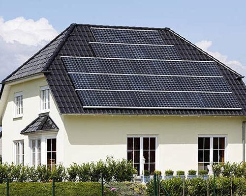 آبگرمکن خورشیدی مدار بسته روی سقف خانه سفید و باغچه سبز