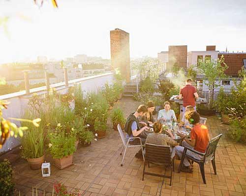 خانواده ای در حال غذا خوردن در روف گاردن یا بام سبز منزل خود هستند