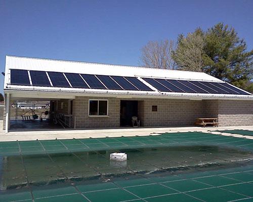 استخر خورشیدی و پنل های خورشیدی روی بام خانه سفید و درخت سبز