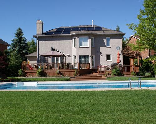 استخر خورشیدی و درخت سبز و کلکتور های خورشیدی روی بام خانه طوسی