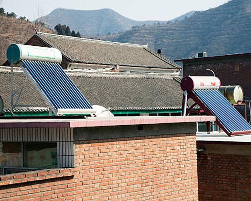 آبگرمکن خورشیدی روی سقف خانه های روستایی و جنگل سبز