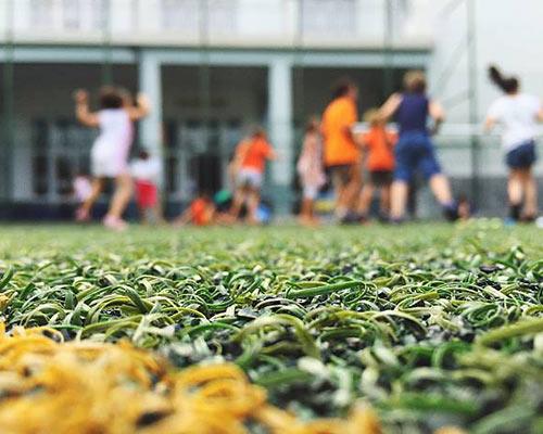 کودکان در حال فوتبال بازی هستند بر روی چمن مصنوعی زیبا و جذاب
