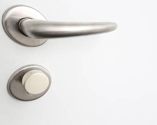 دستگیره درب سفیدی که با وجود آن ، درب به راحتی باز و بسته می شود