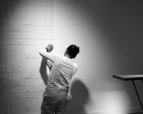 یک خانم در حال انجام دادن نصب کاغذ دیواری سه بعدی می باشد