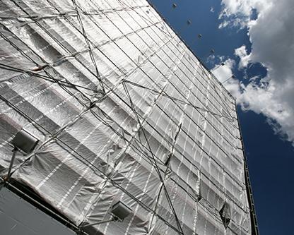 يک آپارتمان چندين طبقه که نماي آن با محافظ هاي پلاستيکي و توري هاي نگهدارنده مصالح پوشيده شده است ، عمليات بازسازي ساختاري در آن در حال انجام است