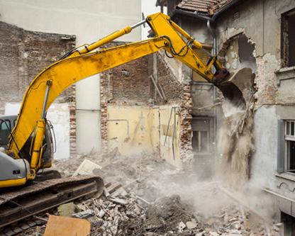 يک بيل مکانيکي زرد در حال تخريب ساختمان متروکه است که اين کار براي انجام بازسازي ساختاري انجام مي شود
