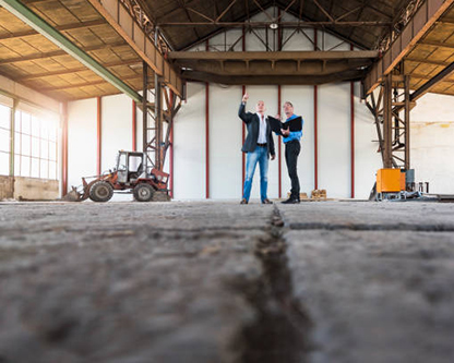 دو مهندس معمار و ناظر بر بازسازي يک کارخانه در حال طراحي دوباره ي نقشه ي ساختمان و بهينه سازي فضا هستند