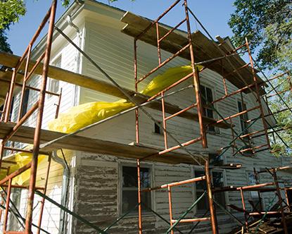 انجام عمليات بهسازي ساختمان روي يک خانه سفيد دوبلکس در يک منطقه سرسبز