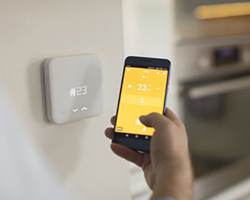 ارتباط ترموستات رادیاتور هوشمند با دستگاه های خانگی دیگر و یک گوشی با صفحه زرد در دست فردی