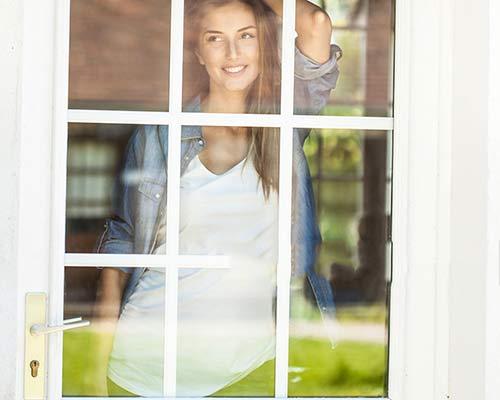 یک خانمی که از پشت درب استیل شیشه ای به مناظر زیبای اطاف نگاه می کند