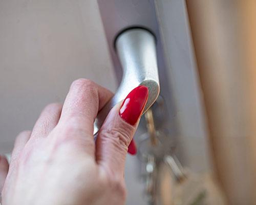 یک خانمی که برای باز شدن درب دستگیره را میفشارد