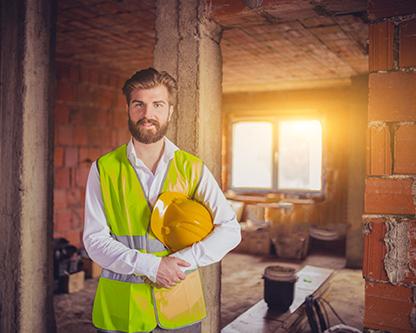 يک معمار جوان که در يک طبقه از يک آپارتمان نيمه ساخت با نماي آجري رنگ ايستاده است ، آموزش ديده براي انواع بازسازي ساختمان است