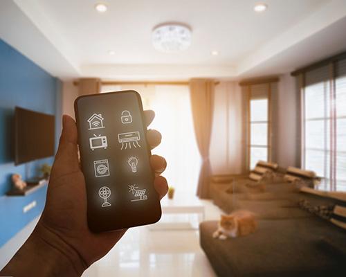 گوشی هوشمند مجهز به برنامه ترموستات در دست یک فرد