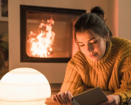 خانمی در جلوی شومینه در حال مطالعه