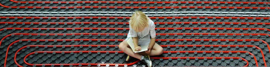 کودکی بر روی لوله کشی گرمایش از کف نشسته است
