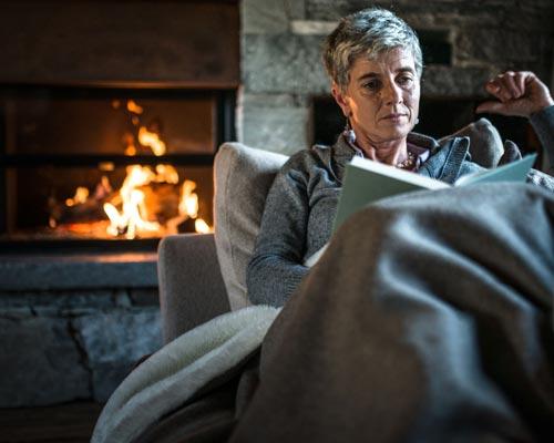 خانمی زیر پتوی خاکستری در حال کتابخوانی پشت به شومینه