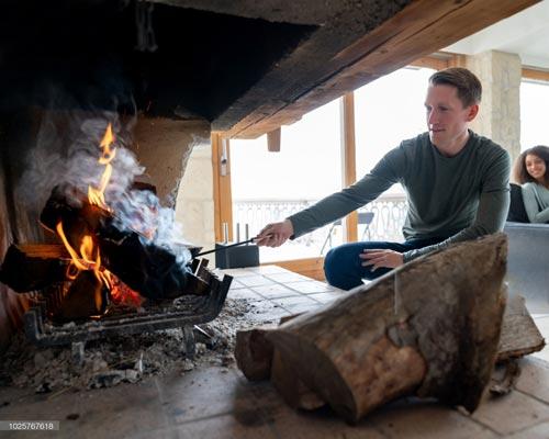 مردی در کنار آتش شومینه چوبی در حال دود کردن