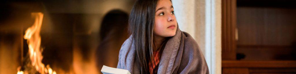 دختری در کنار شومینه در حال مطالعه کتاب است