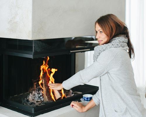 خانمی در حال گرم شدن در مقابل شومینه